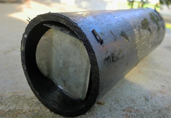 Самодельная кротоловка, сделанная из обрезка металлической трубы.